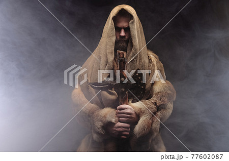 Copy space portrait mysterious man in robes and furs stands and holds an ancient ax in his hands, a dark room with smoke 77602087