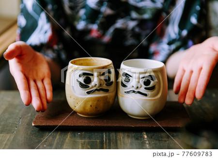 ダルマの顔のカップを紹介する女性の手 77609783