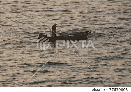 網を引き揚げる漁師 77630868