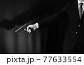 拳銃を構えるスーツの人物 77633554