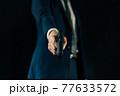 拳銃を構えるスーツの人物 77633572