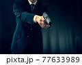 拳銃を構えるスーツの人物 77633989