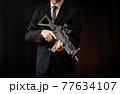 アサルトライフルを構えるスーツの人物 77634107