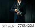 アサルトライフルを構えるスーツの人物 77634228