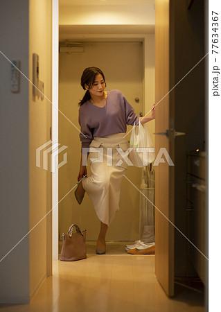 帰宅して玄関で靴を脱ぐ女性 77634367