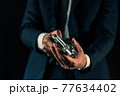 拳銃を構えるスーツの人物 77634402