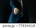 拳銃を構えるスーツの人物 77634418