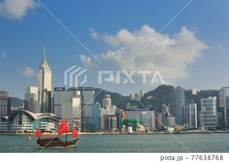 香港・高層ビル街をバックにヴィクトリア・ハーバーを往くジャンク船 77638768