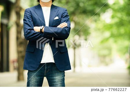 新緑のビジネス街で腕組みして立っている男性 77662227