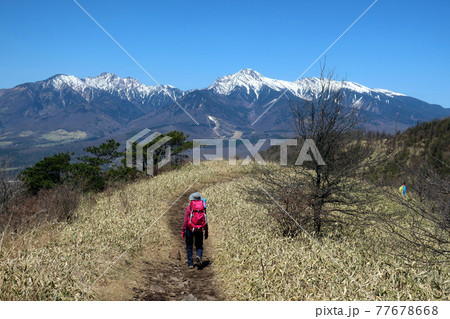 長野の飯盛山から見る八ヶ岳と女性登山者 77678668