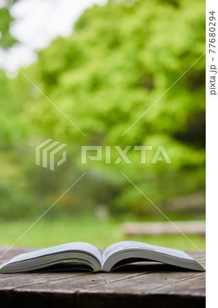 庭のテーブルに置いている開いた本の風景 77680294