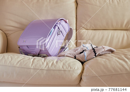 リビングのソファーに置いている小学生のランドセルと服 77681144
