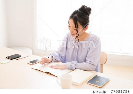 学習中にノートにペンで文字を書く女性 77681733