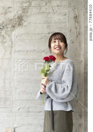コンクリートの壁の前で薔薇を2輪持ち立っている若い女性 77684410