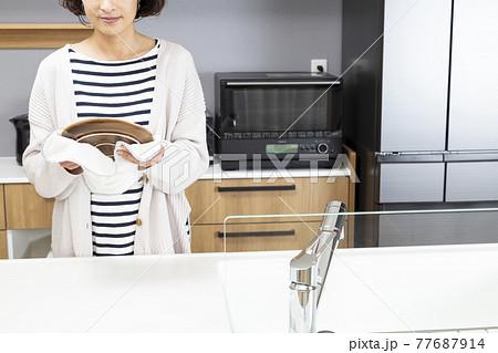 キッチンで皿を拭く女性 77687914