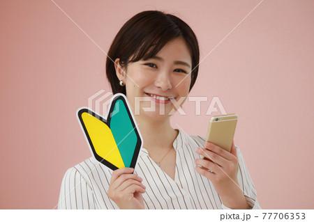 スマートフォンと初心者マークを持つ女性 77706353