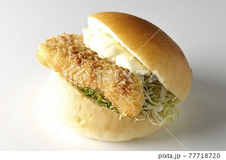 たっぷりのタルタルソースと白身魚のフライがはさまったハンバーガーを白背景で撮影 77718720