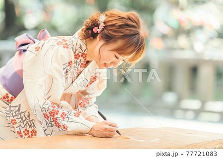 短冊に願いを書く浴衣姿の女性 77721083