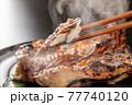 焼きたての魚を箸で摘むシーン 77740120