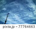 青空に薄く伸びて広がる雲と画面の端に建つ鉄塔 77764663