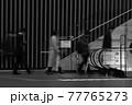 都会を行き交う人々のモノクロ写真 77765273
