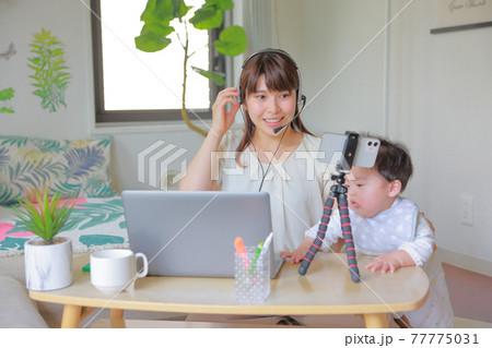 スマホでオンラインミーティング_ヘッドセットに手を掛ける母親とPCに手を伸ばす乳児 77775031