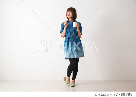 ハブラシとカップを手に持つ若い女性 77789795