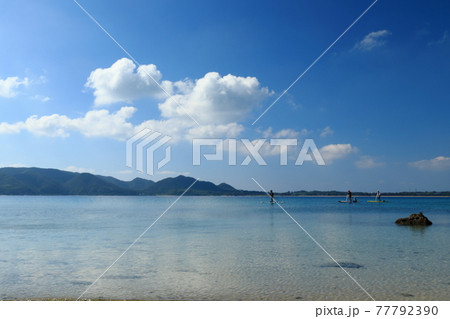 奄美大島倉崎海岸の青く澄んだ海でマリンスポーツを楽しむ人たち 77792390
