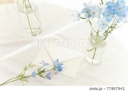 花瓶にいけられた青い花と白い手紙 77867942