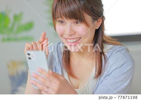 スマホを嬉しそうにタップしようとする若い女性 77871198