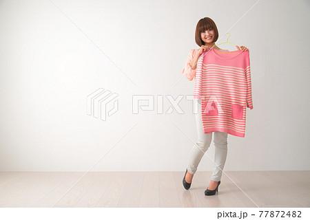 ピンク色のボーダー柄の洋服を体の前で合わせてみる若い女性 77872482