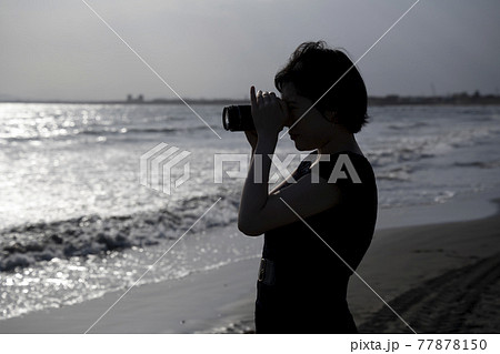 砂浜でデジカメで撮影するカメラ女子(シルエット) 77878150
