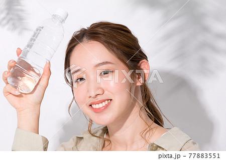 水分補給のために水のペットボトルを手に持つ若い女性 77883551