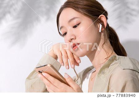 スマホでお気に入りの音楽を聴く若い女性 77883940