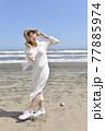 九十九里浜を散歩するワンピース姿の若い笑顔の女性 77885974