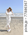 九十九里浜を散歩するワンピース姿の若い笑顔の女性 77886367