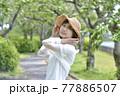 初夏の新緑の公園と麦わら帽子を被った笑顔の女性 77886507