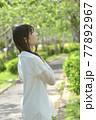 初夏の新緑の公園と白いワンピース姿の若い女性 77892967