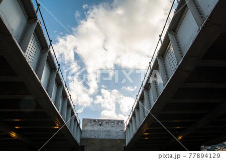 二つの鉄橋の間から見える青空と大きな雲 77894129