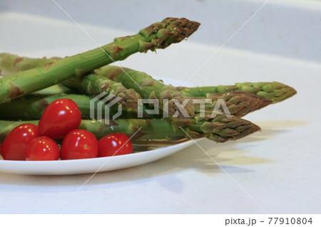 皿の上のみずみずしいアスパラガスとミニトマト 77910804