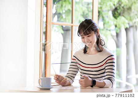 カフェ 次世代タブレット(イメージ)を使う若い女性 合成用 77911102