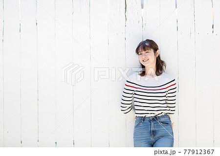 白壁に寄りかかる女性 77912367