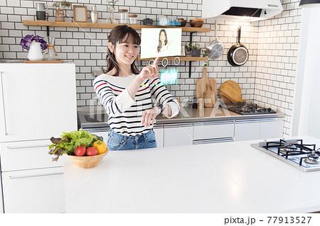 キッチンでスマートウオッチを使う女性 77913527