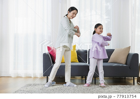 Asian mother and young daughter dancing together 77913754
