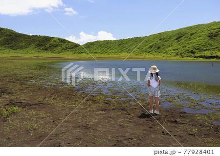 阿蘇草千里ヶ浜の草原にたたずむ女の子 77928401
