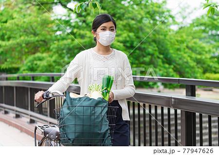 買い物袋を自転車のカゴ(籠)に入れて引いて歩く若い女性  77947626