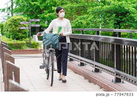 買い物袋を自転車のカゴ(籠)に入れて引いて歩く若い女性  77947633