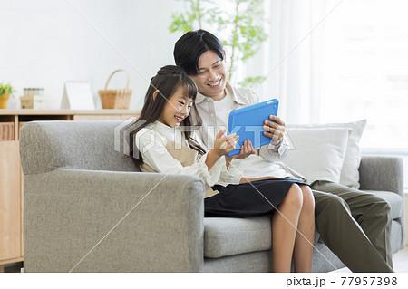 タプレットPCを見る親子 77957398