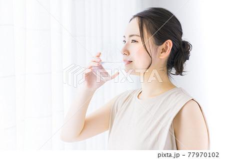 ミネラルウォーターを飲む若い女性 77970102