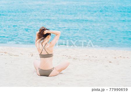砂浜に座る水着姿の女性 77990659